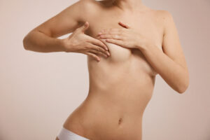 Woman checking her breast  Featured image for What is Micromastia? Blog
