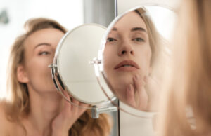 [Woman Looking Longingly Into Mirror, Contemplating Her Facial Complexion]   Featured image for Taking Care of Your Face   Blog